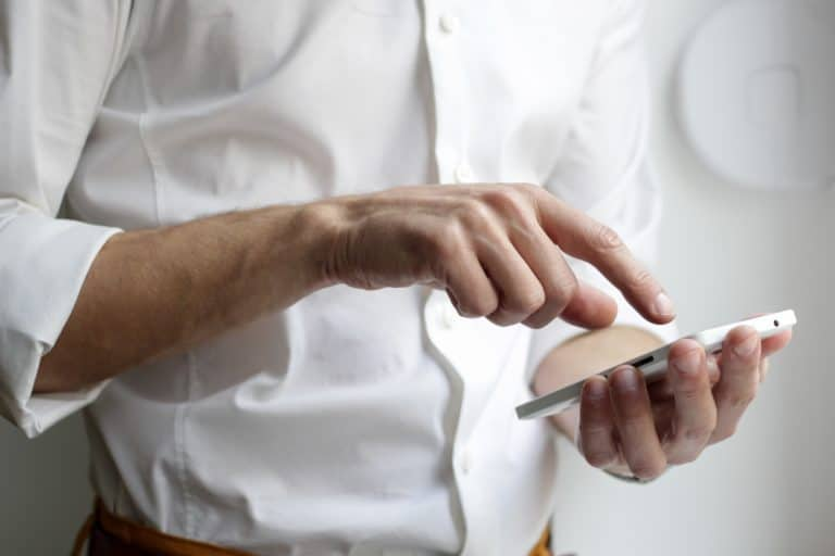 person holding white Android smartphone in white shirt
